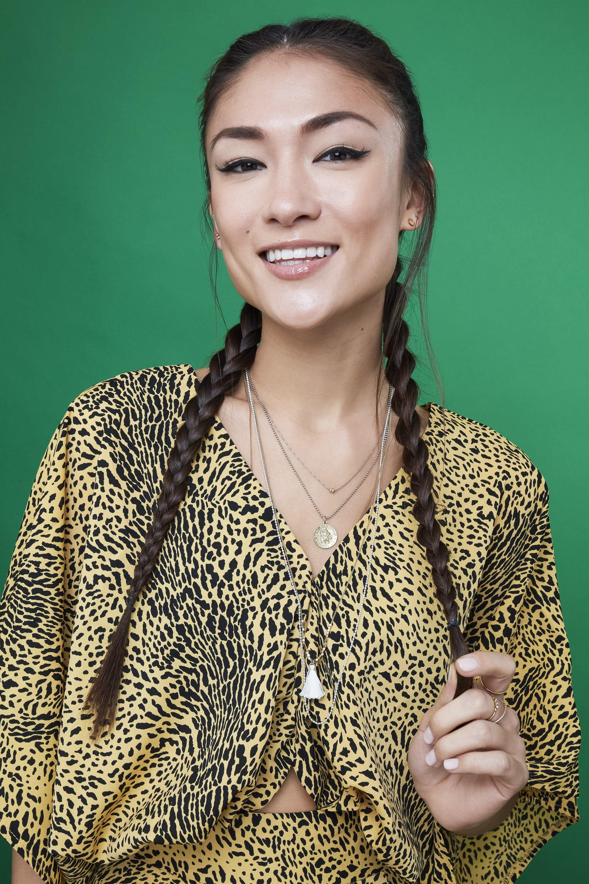 Braids for long hair: Woman with very long dark brown hair in boxer braids wearing a pattern top against a green backdrop.