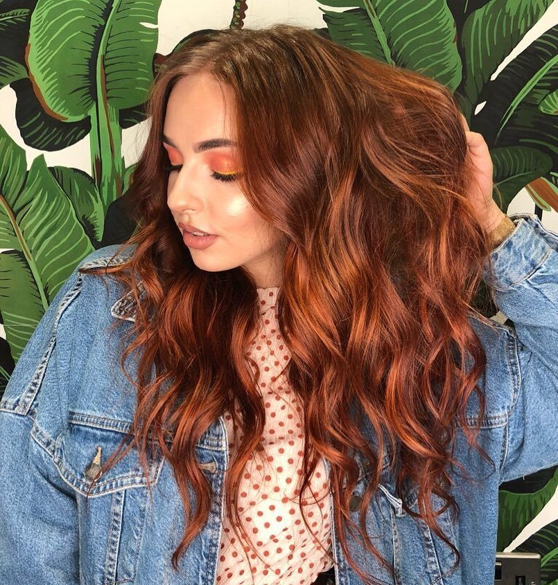Woman with long beachy brown hair with fiery pumpkin highlights