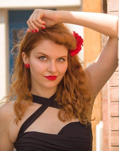 redhead girl with curly shoulder length hair styled into a vintage suicide roll with a red flower hair clip