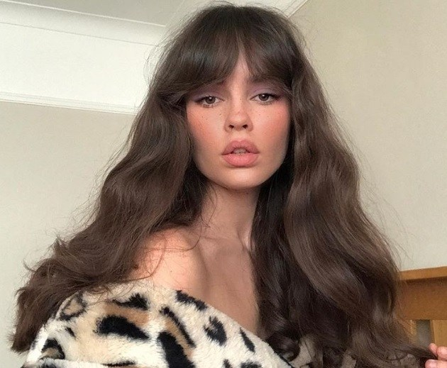 Types of bangs: Woman with long chestnut brown wavy hair with Bardot bangs, wearing a leopard print jacket