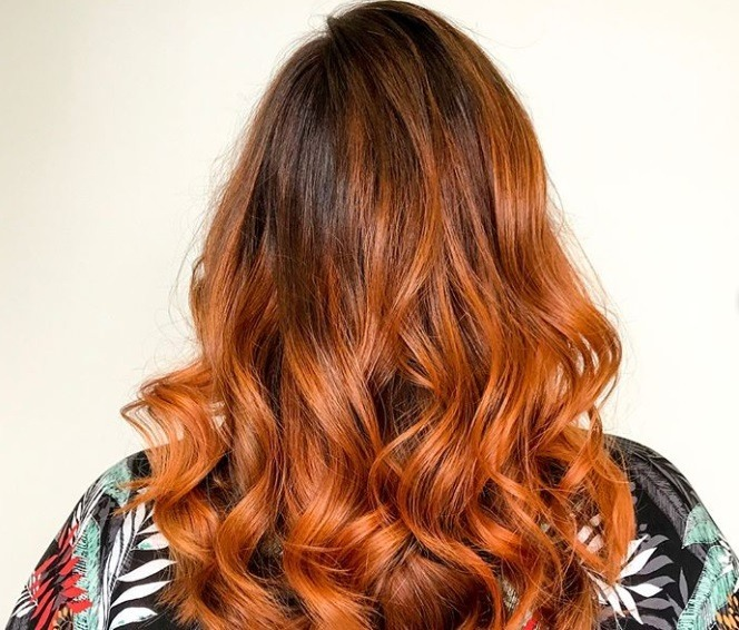 Pumpkin spice latte hair: Backshot of a woman with fiery ginger pumpkin hair styled into loose curls, wearing floral top and posing in a salon