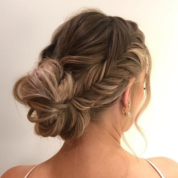Updos for thin hair: Back side view of a woman with dark blonde hair in a French fishtail braided updo with wispy strands