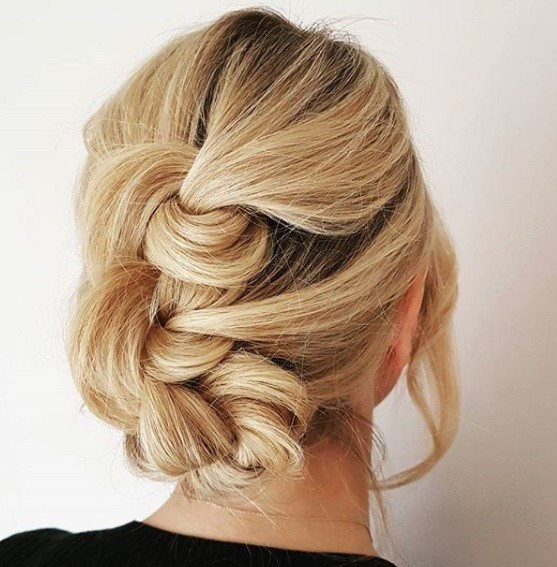 Updos for thin hair: Back view of a blonde woman with her hair in a knotted updo