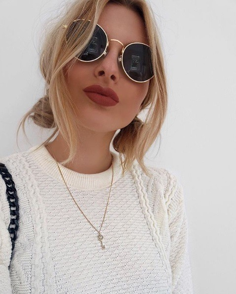 Updos for thin hair: Blonde woman with two low buns and wispy front bangs, wearing a white cableknit jumper and retro sunglasses