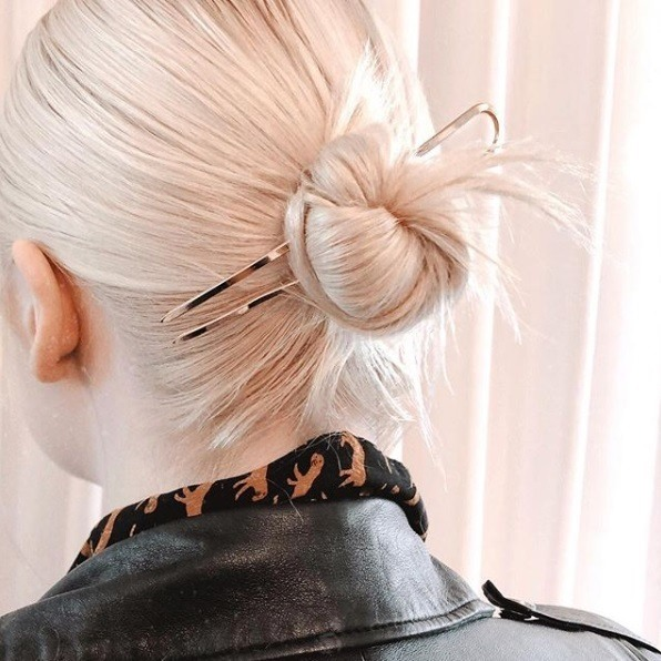 Updos for thin hair: Close-up back view of a woman with platinum blonde white hair in a sleek bun with an oversized gold hair pin