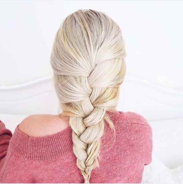 Updos for thin hair: back view of a girl with platinum blonde long hair in a single plait, wearing a fluffy pink jumper