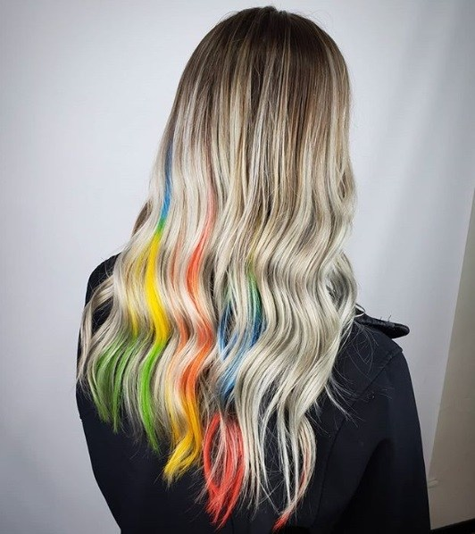 Woman with long blonde hair with peekaboo rainbow highlights
