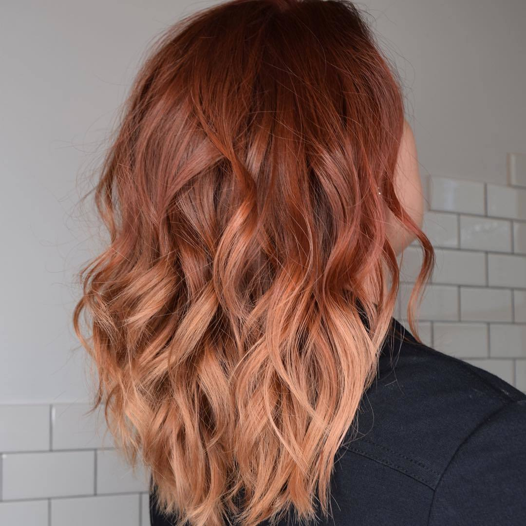 Woman with rose gold pumpkin spice wavy hair