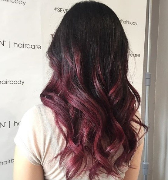 back view of a woman with long dark brown to deep red ombre curled hair