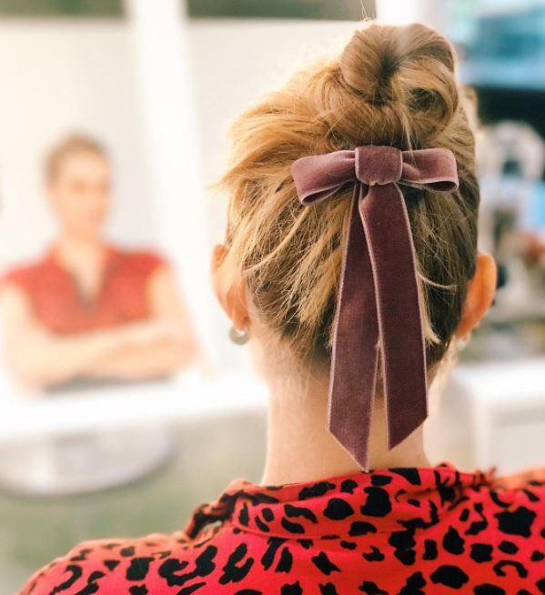back view of blonde hair in high bun with pink velvet bow under bun