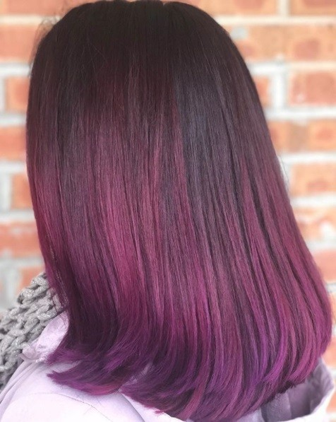 close up back view of a woman with straight shoulder length red and purple hair